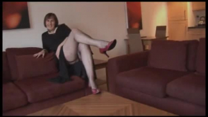 Brunette tranny with glasses strips and spreads her pussy