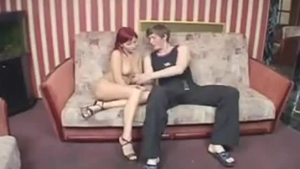 Busty red haired mature with kiss line shaved twat brings a bottle to the couch