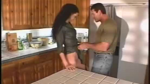Fit brunette is squeezing her boobs in front of her planter, while getting nude in the kitchen