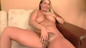 Blondie with hairy pussy rubs dripping pussy indoors and at the same time masturbates in